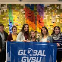 Eight GVSU students holding Global GVSU flag at museum in Bilbao, Spain